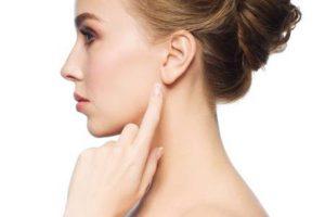 La santé, les gens et le concept de la beauté - belle jeune femme pointant du doigt son oreille sur fond blanc Banque d'images - 62831837